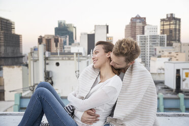 Romantic couple sitting on rooftop terrace, enjoying the view - WESTF23153