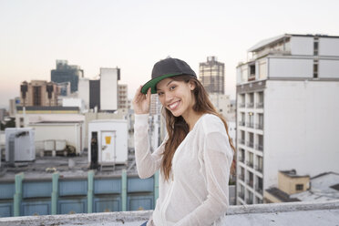 Young woman standing on a rooftop terrace, smiling - WESTF23156