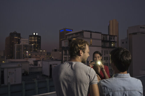 Young woman taking pictures of friends at a rooftop party - WESTF23159