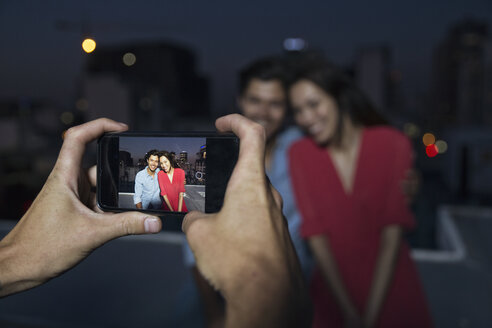 Young man taking picture of a couple at a rooftop party - WESTF23162