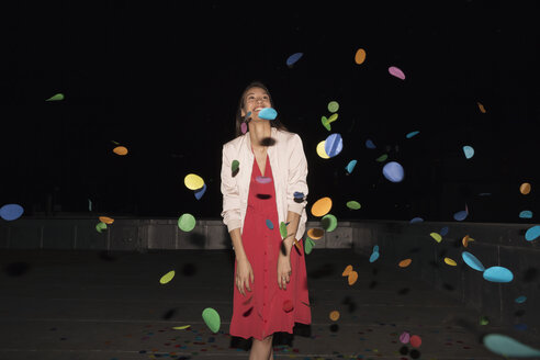 Young woman standing on a rooftop terrace with flying confetti - WESTF23165