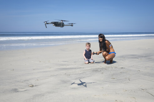 Young woman and boy on the beach flying drone - ABAF02154