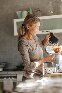Happy woman at home in kitchen preparing coffee - JOSF00764
