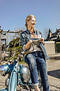 Smiling woman with vintage motorcycle having a coffee break - JOSF00779