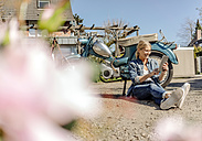 Smiling woman sitting at vintage motorcycle using tablet - JOSF00782