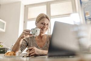Woman at home having breakfast and using laptop - JOSF00788