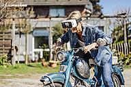 Happy woman on vintage motorcycle wearing VR glasses - JOSF00806