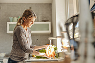 Woman in kitchen washing carrots - JOSF00809