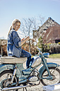 Smiling woman on vintage motorcycle having a coffee break - JOSF00812