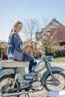 Smiling woman on vintage motorcycle having a coffee break - JOSF00812