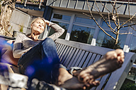 Woman relaxing on garden bench - JOSF00815