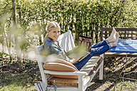 Smiling woman using laptop on garden bench - JOSF00818