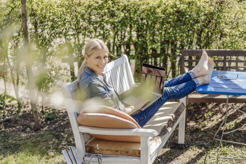 Smiling woman using laptop on garden bench - JOSF00818