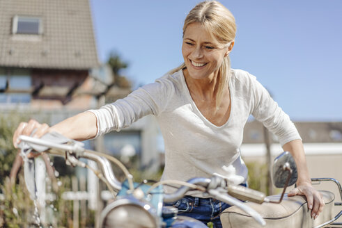 Smiling woman cleaning vintage motorcycle - JOSF00821