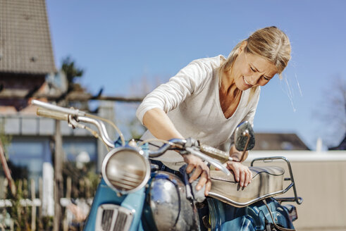 Smiling woman cleaning vintage motorcycle - JOSF00824
