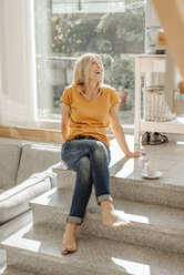 Happy woman sitting on stairs at home - JOSF00827