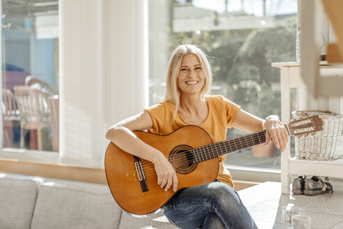 Smiling woman at home with guitar - JOSF00830