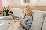 Smiling woman at home on couch with tablet - JOSF00833
