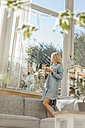 Woman at home standing on couch eating fruit salad looking out of window - JOSF00839