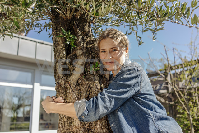 Woman in garden hugging a tree - JOSF00845