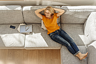 Smiling woman at home lying on couch - JOSF00851