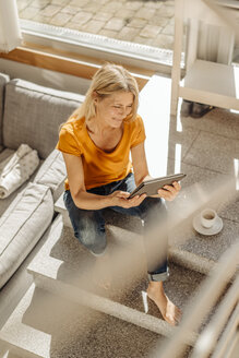 Woman at home with cup of coffee and tablet - JOSF00860