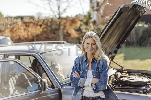 Smiling woman standing at vintage car - JOSF00866