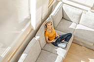 Woman at home sitting on couch with headphones and tablet - JOSF00869
