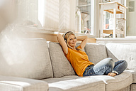 Woman at home sitting on couch wearing headphones - JOSF00872