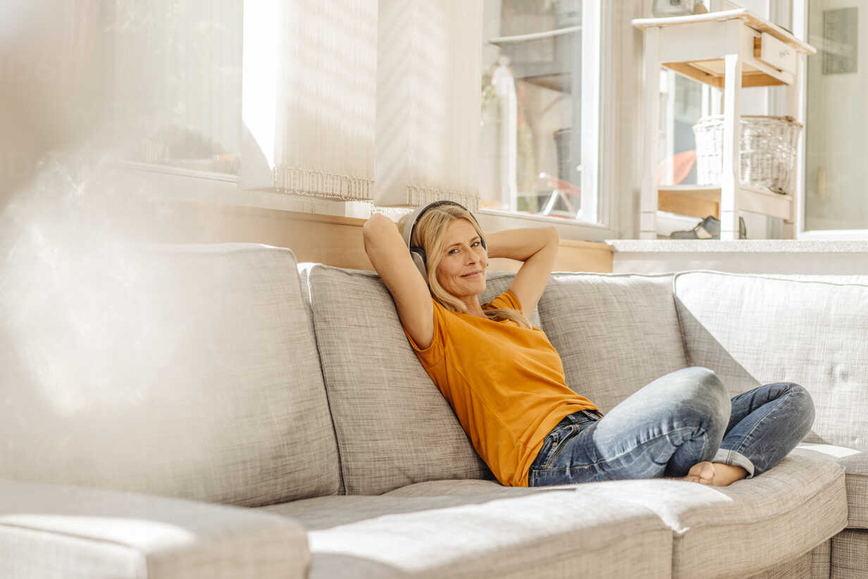 Woman at home sitting on couch wearing headphones - JOSF00872 - Joseffson/Westend61
