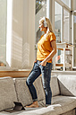 Woman at home standing on couch wearing headphones - JOSF00875