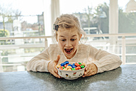 Excited girl with chocolate Easter eggs on table - JOSF00881