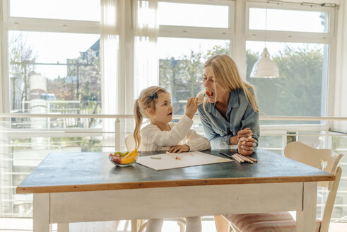 Mature woman and girl at home at the table eating and drawing - JOSF00884