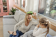 Playful mature woman and girl at home on couch - JOSF00896