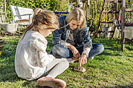 Smiling mature woman and girl with tortoise in garden - JOSF00899