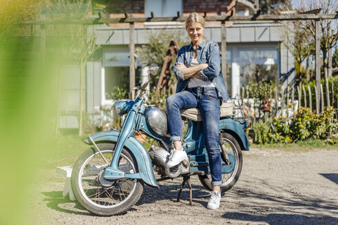 Smiling woman with vintage motorcycle - JOSF00905