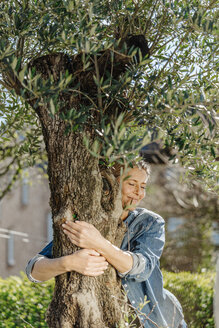Woman in garden hugging a tree - JOSF00911