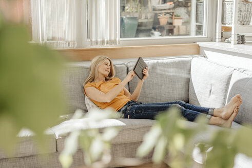 Woman at home on couch with cup of coffee and tablet - JOSF00917