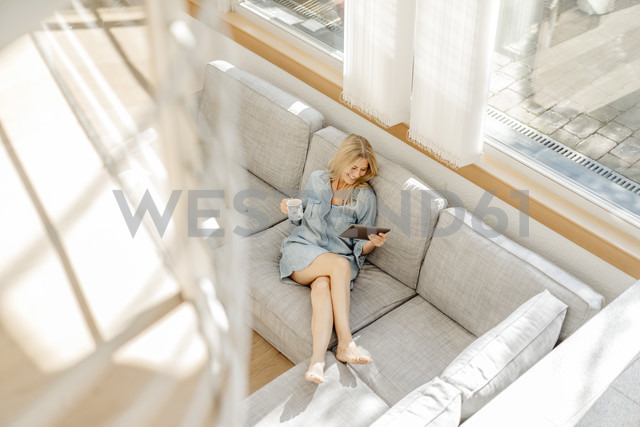Woman at home on couch with cup of coffee and tablet - JOSF00920