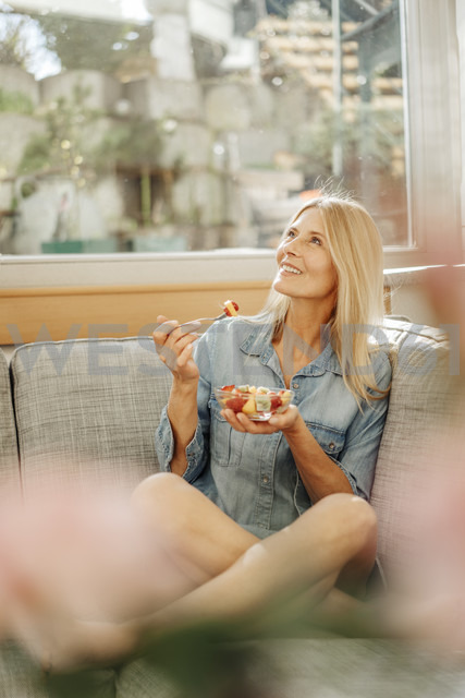 Woman at home sitting on couch eating fruit salad - JOSF00926
