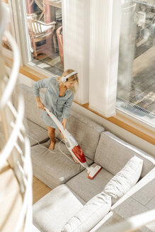 Woman at home wearing headphones hoovering the couch - JOSF00929