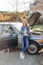 Smiling woman with girl standing at vintage car - JOSF00941