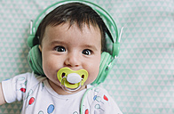 Portrait of baby girl with headphones and pacifier - GEMF01610