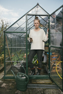 Young woman standing in her greenhouse - MFF03485