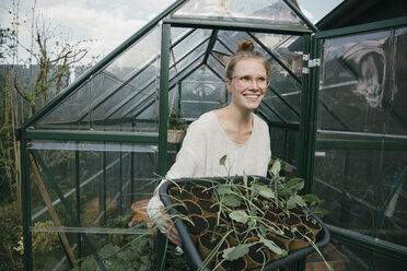 Portrait of happy young woman with potted seedlings in front of greenhouse - MFF03488