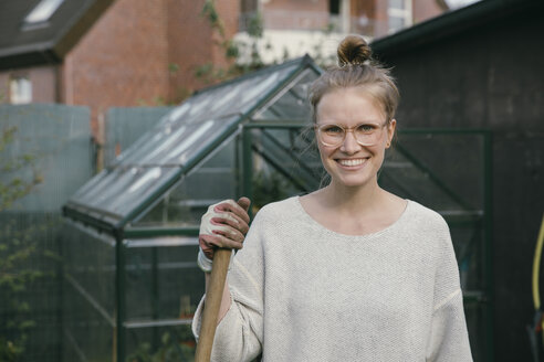 Portrait of smiling young woman in front of greenhouse - MFF03491