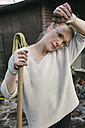 Portrait of tired young woman with rake in the garden - MFF03494