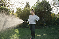 Young woman sprinkling lawn in the garden - MFF03500