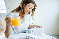 Smiling young woman with glass of orange juice looking at agenda - KIJF01471
