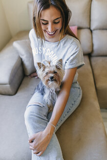 Smiling young woman sitting on couch with her Yorkshire Terrier - KIJF01480